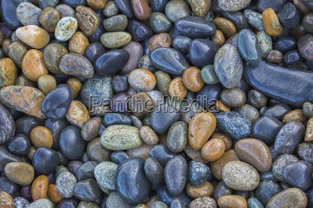 multi coloured rocks line the shoreline