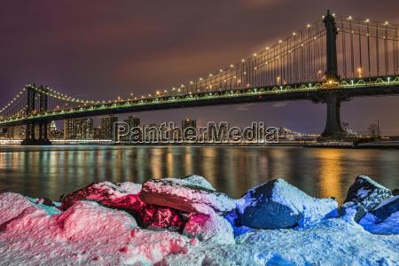 manhattan bridge by snow covered rocks