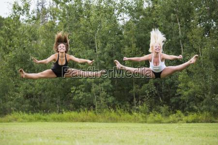 zwei teenage gymnasts ueben ihre routinen