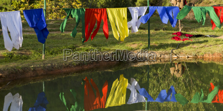 colourful prayer flags hanging and reflected