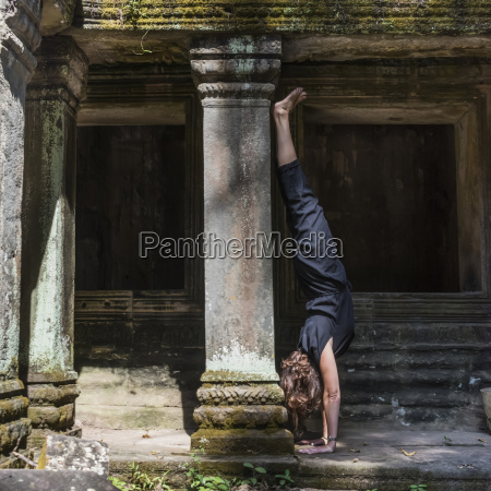 a woman does a hand stand