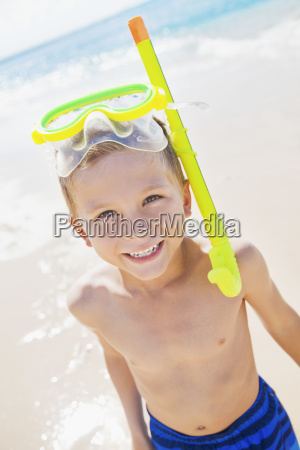 a young boy smiling with snorkel