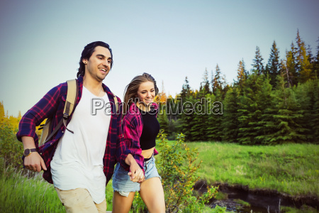 young couple running while holding hands
