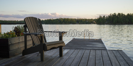 a wooden adirondack chair sits on