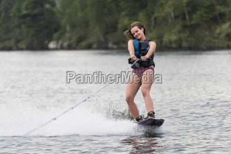 a teenage girl wakeboarding behind a
