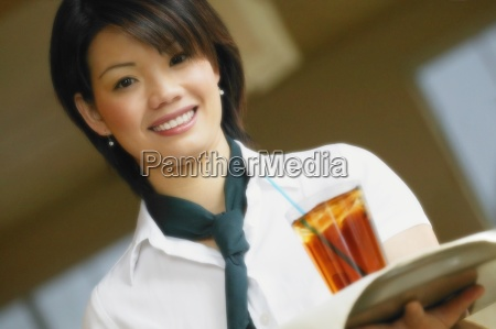 asian woman carrying drink on tray