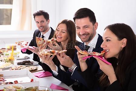 businesspeople enjoying slice of pizza