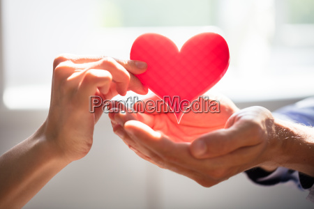 woman giving heart on mans hand