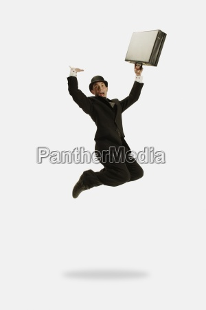 businessman jumps with briefcase in hand