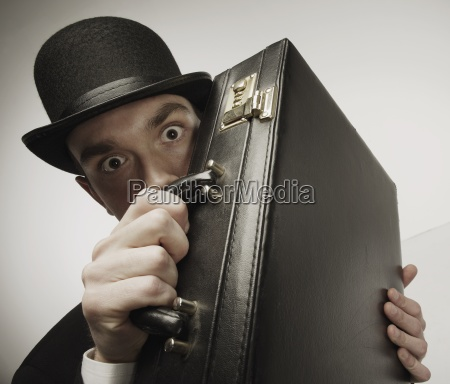 man peering over his briefcase