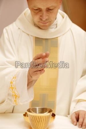priester der ueber kommunion betet