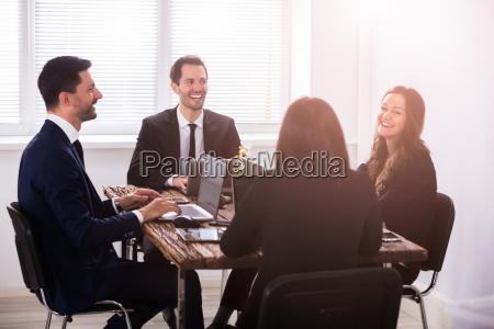 businesspeople attending meeting in office
