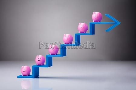 many pink piggybanks on blue arrow