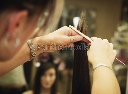 a hair stylist styling a young