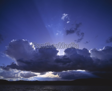 storm clouds with sun rays lake