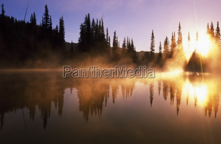 sunbeams through mist on lake