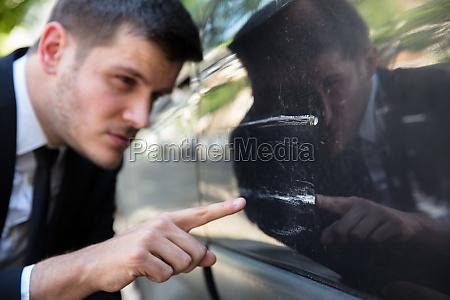 man inspecting damaged car