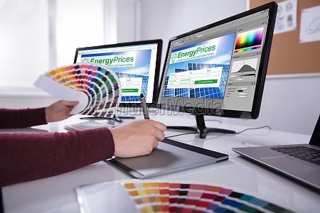 designer der auf mehreren computerbildschirmen arbeitet