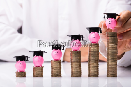 person placing piggybank with graduation hat