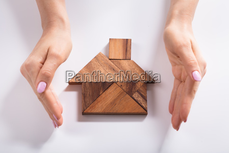 woman protecting house made of wooden