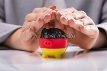 woman protecting piggybank painted with german