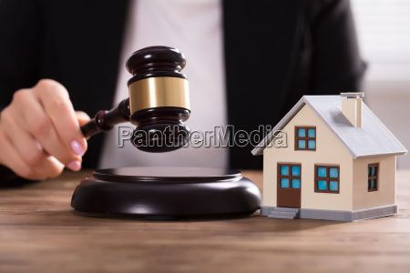 judge striking gavel near house model