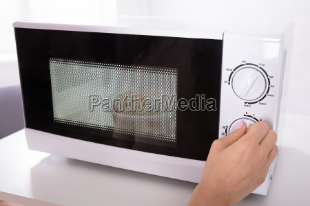 woman using microwave oven for preparing