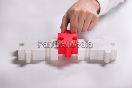 person placing red piece between white