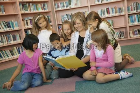 kinder werden in eine bibliothek gelesen