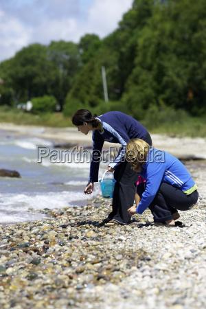 two women picking up rocks on