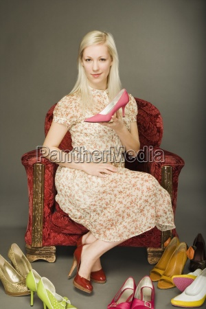woman holding high heel shoe with