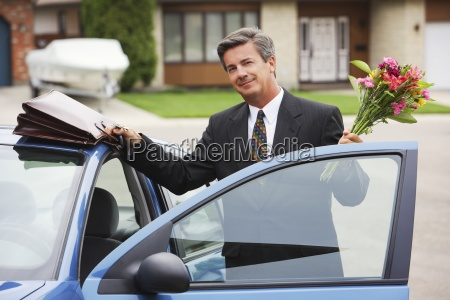 businessman holding bouquet smiling