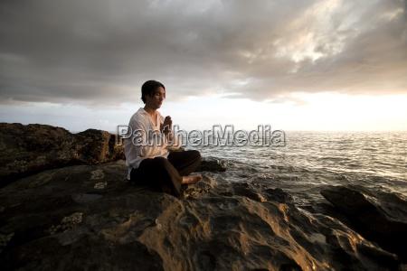man praying on shoreline koh lanta