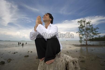 man praying by the beach koh