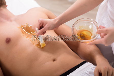 beautician applying wax on mans chest