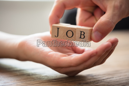businessperson giving wooden block mit job