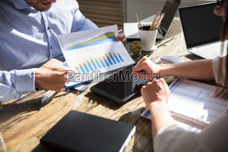 businessman showing graph to his colleague