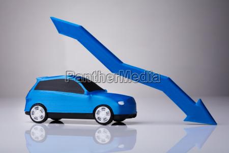 abnehmender pfeil ueber blaues auto vor
