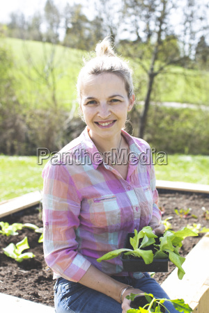 young pretty blond woman is planting