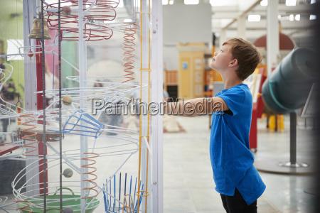 junge stehend blickende wissenschaftsausstellung seitenansicht
