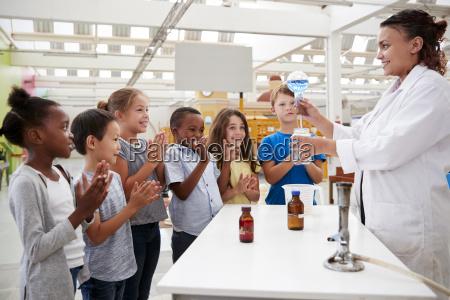 labortechniker zeigt begeisterten kindern ein wissenschaftliches