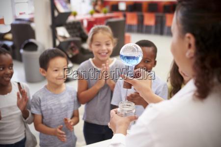 labortechniker zeigt aufgeregten kindern ein experiment