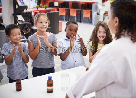 klassenkameraden applaudieren lehrer nach einem naturwissenschaftsexperiment