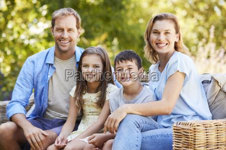 junge weisse familie sitzt im garten