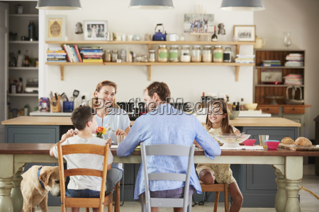 family with dog eating together at