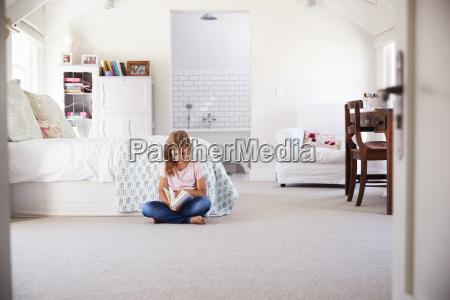 junges maedchen liest ein buch allein