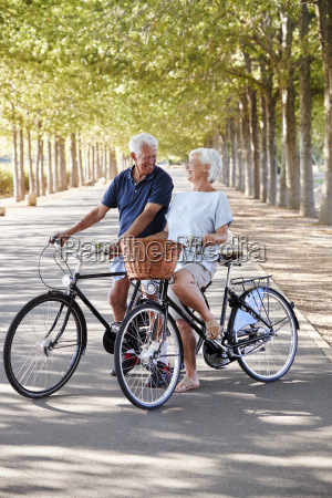 smiling senior couple cycling on country