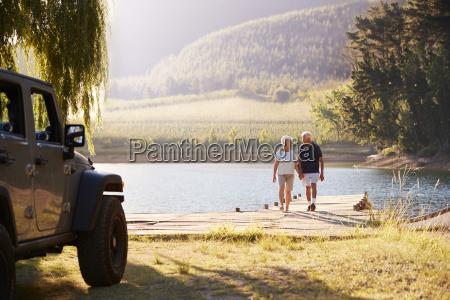 senior couple walking by lake at