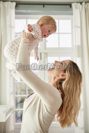 mother lifting baby daughter in the