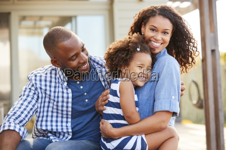 black family embracing outdoors smiling to